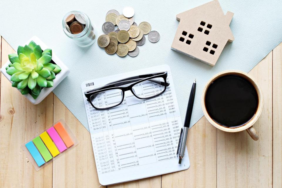 Paperwork, glasses, sticky notes, coins, and a small wooden house on a desk